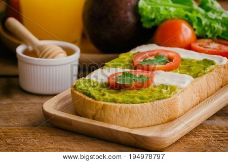 Open sandwich for breakfast or lunch. Sandwich spread with cream cheese avocado and tomato.Avocado and cream cheese open sandwich style serve with orange juice on rustic wood table in close up view. Delicious sandwich ready to served.