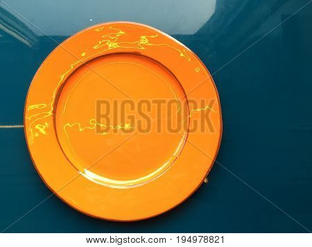 Orange glossy plate with brown rims. The plate stands on a blue glossy surface. Shooting from the top.