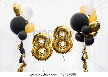 Decoration for birthday, anniversary, celebration of theE eighty-eighth, infinity anniversary, white background, gold and black balloons with tassels