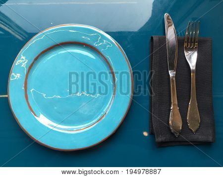 A beautiful glossy light blue dish with cutlery on a dark napkin. The silver knife and fork lie on a black napkin. The plate stands on a blue glossy surface. Shooting from the top.