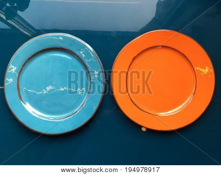 Orange and light blue glossy plates stand on the dark blue surface of the table. Shooting from the top.