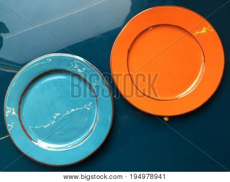 Two empty ceramic plates stand on the table. Orange and light blue glossy plates stand on the dark blue surface of the table. Shooting from the top.