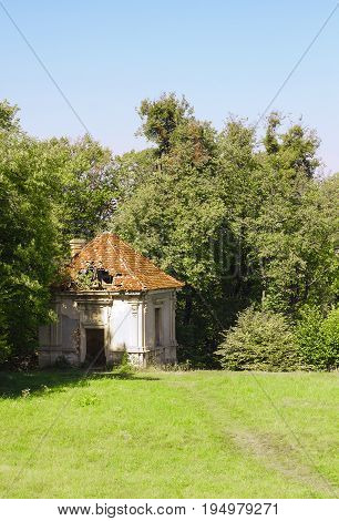 Old abandoned lodge with slate roof stands near forest