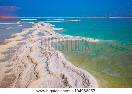 Summer day at the famous seaside resort on the Dead Sea. The evaporated salt has developed into fantastic patterns. The concept of medical and ecological tourism