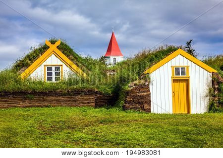 Church bell tower with gabled red roof. The old village of  houses covered with turf. Ethnographic Museum-estate Glaumbaer, Iceland. The concept of the historical and cultural tourism