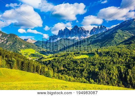 The green valley is surrounded by a dentate wall of dolomite rocks. Warm autumn in the Dolomites, the Val de Funes.  The concept of ecological tourism