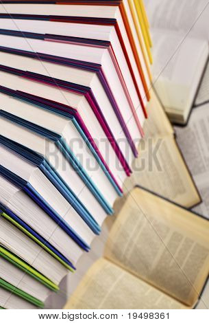 Close-up of curve aligned in rainbow colors paper wrapped books with  open books below, top-down view, PHOTOGRAPH, NOT 3D RENDER.