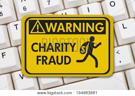 Charity Scam warning sign A yellow warning sign with text Charity Fraud and theft icon on a keyboard 3D Illustration