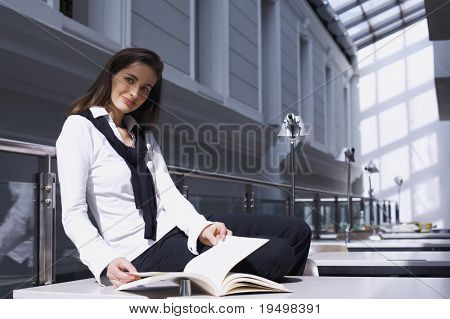Smiling pretty girl sitting on desk in modern university library studying a book.