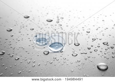 Contact lenses and drops of water on gray background