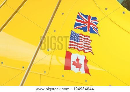 British American and Canadian flags on a bright yellow metallic aircraft panel