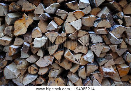 Stack of firewood close-up under the fallen snow