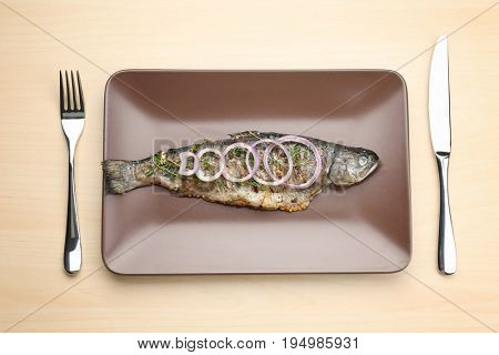 Plate with tasty fried fish and cutlery set on light background