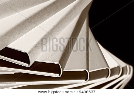 Black & White art conversion: Close-up of winding stack of real books on black background, side view.