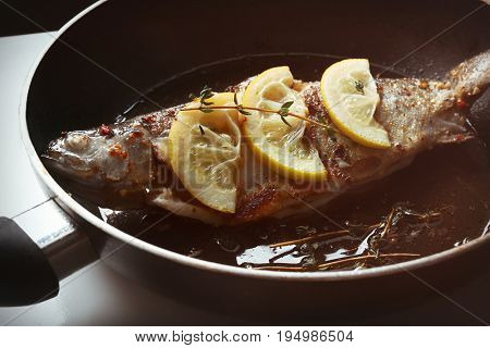 Cooking trout fish on frying pan, closeup