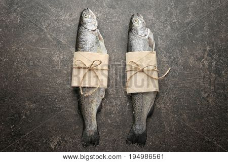 Fresh trout fish wrapped in paper on gray background