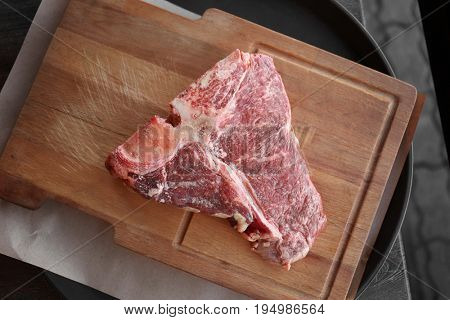 Fresh raw beefsteak on wooden board, top view
