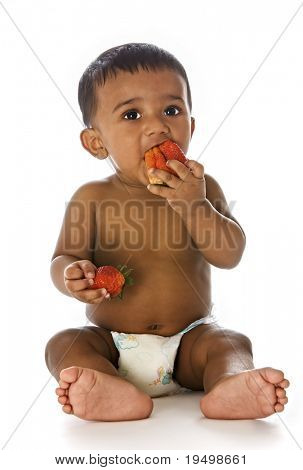 Adorable healthy Indian baby sitting on floor and eating strawberries, isolated on white background.