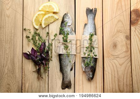 Composition with fresh trout fish wrapped in paper on wooden background