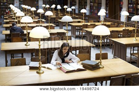 Attractive student sitting at desk in old university library and studying books.