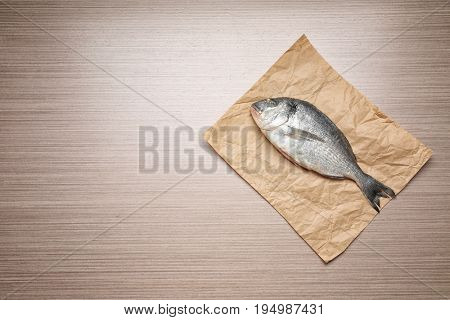 Parchment with fresh dorado fish on wooden background