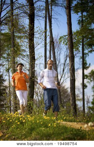 Woman and man jogging in forest with beautiful dandelions in foreground.