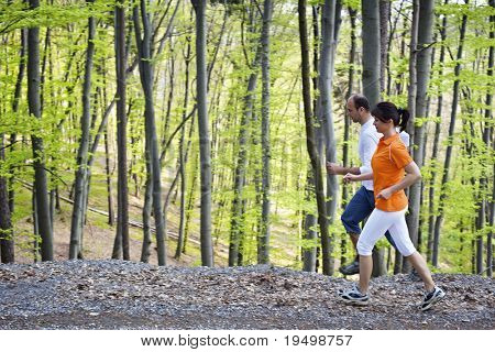 Woman and man jogging on gravel path beside each other with green beech forest in background.
