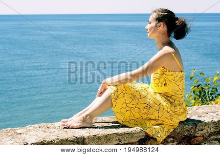 Beautiful young woman sitting on a parapet and admiring the sea