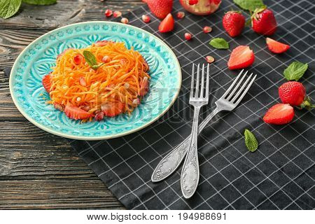 Blue patterned plate with yummy carrot strawberry salad on black checkered napkin