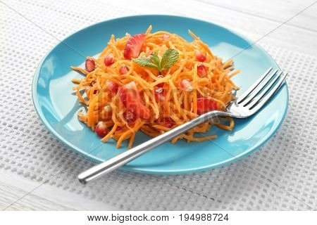 Blue plate with yummy carrot strawberry salad on white table