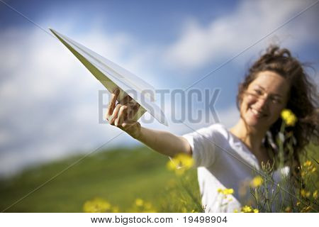 Jolly woman in green field holding up a paper plane into the blue sky expressing liberation.