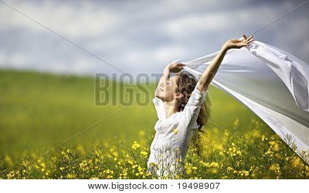 Young happy Woman standing in gelben Raps Feld hält ein weißes Stück Stoff in der Wind-expre