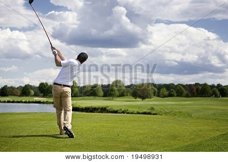 Golf player teeing off golf ball from tee box, wonderful cloud formation in background.