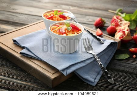 Yummy carrot strawberry salad in cute white bowls on wooden table