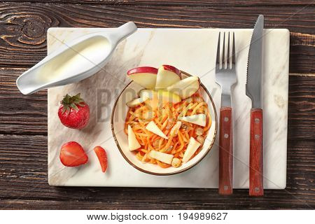 Yummy carrot raisin salad with apple in cute white bowl on wooden table