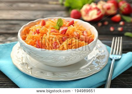 Yummy carrot strawberry salad in beautiful bowl on wooden table