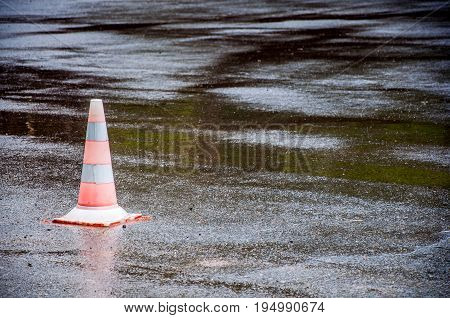 A General View At The Restrictive Road Cone Placed On Asphalt With Puddles. Green Trees And Cone Ref