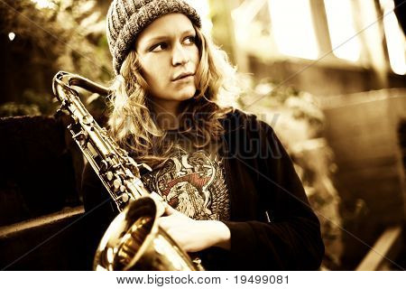 Cool girl holding saxophone in shabby factory, looking left.