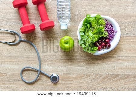 Healthy lifestyle sport equipment fitness sneakers green apple fresh water and healthy food on wood background. Healthy Concept.