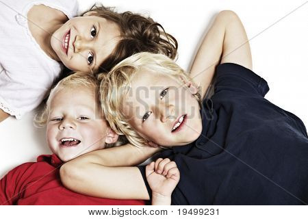 Close-up of happy children lying on floor in studio and looking up, isolated on white background, top view.