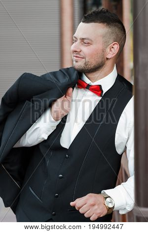 Young stylish man in a suit. Portrait of the groom. The groom is holding his jacket on his shoulder side view looking to the side. Hand with golden watch. Business concept.