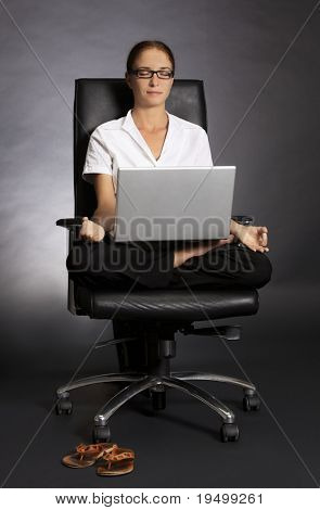 Stressless at work: Attractive office woman sitting in office chair in yoga lotus posture with laptop on her lap.