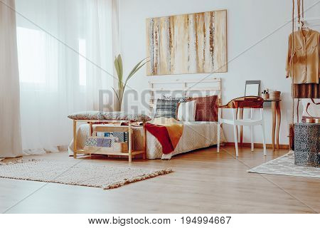 Colorful decorative pillows on the big wooden bed in spacious room