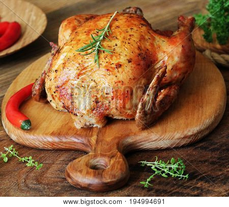 Whole roasted chicken with herb on cutting board .