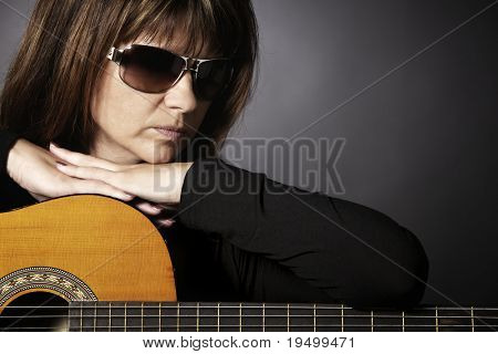 Close up of cool young woman in black leaning on guitar looking down, isolated on black.