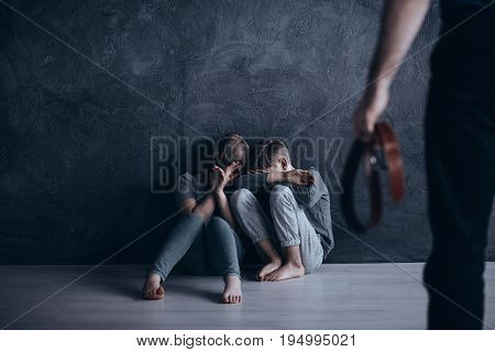 Father holding his belt in front of terrified children