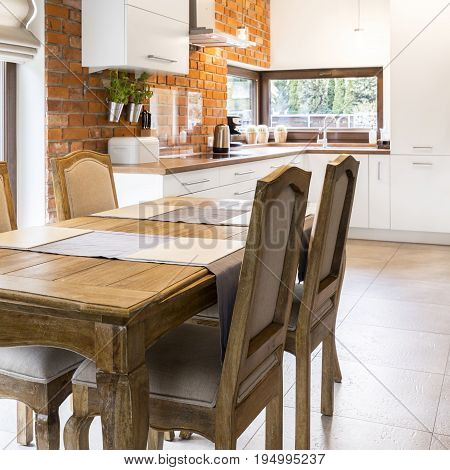 Spacious dining hall with vintage wooden table in front of stylish kitchen