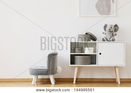 White cupboard with boxes standing next to a little grey chair