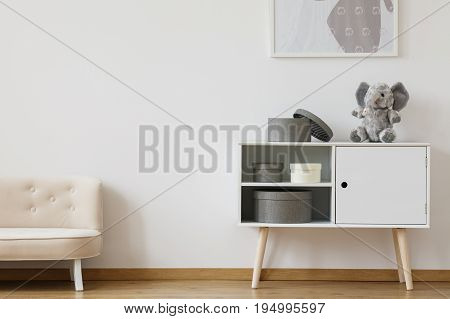Comfy white small couch standing in kid room with cabinet