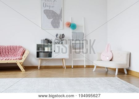Decorative pink rabbit cushion lying on bright small sofa in baby room